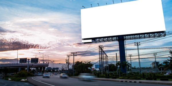 LED lit billboard above road at sunset